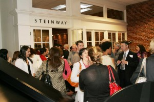 Members and guests enjoy conversation and the ambiance of the Steinway showroom