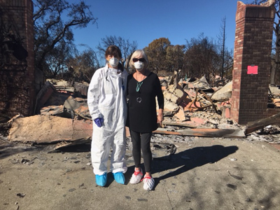 Suzanne O'Brien standing in front of what's left of her home. Survivor stories from The Great Wine Fires of 2017 as told to The Luxury Marketing Council of San Francisco